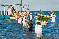 Candomblé devotees carry flower baskets onto a boat during the ritual ceremony in honor to Yemanjá, the goddess of the sea, in Amoreiras, Bahia, Brazil, 3 February 2012. Yemanjá, originally from the ancient Yoruba mythology, is one of the most popular ?orixás?, the deities from the Afro-Brazilian religion of Candomblé. Every year on February 3rd, hundreds of Yemanjá devotees participate in a colorful celebration in her honor. Faithful, usually dressed in the traditional white, gather at the beach on Itaparica island to leave offerings for their goddess. Gifts for Yemanjá include flowers, perfumes or jewelry. Dancing in the circle and singing ancestral Yoruba prayers, sometimes the followers enter into a trance and become possessed by the spirits. Although Yemanjá is widely worshipped throughout Latin America, including south of Brazil, Uruguay, Cuba or Haiti, the most popular cult is maintained in Bahia, Brazil.