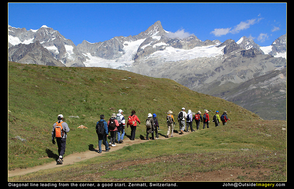 Switzerland, Matterhorn.  <br /> Sometimes we all get a little tired of crowds, well maybe not all of us. The blue sky acts as an overhead frame, just enough to act as a border or frame over the mountain range. If there were impressive clouds, I would have included more sky.  The trail and hikers form a diagonal line coming  from the left corner. A simple, but effective compositional tool. The hikers' colorful clothes brighten the image.