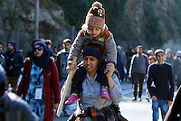Pictured: A young mother walks on the motorway with her young child on her shoulders Thursday 25 February 2016<br /> Re: Hundreds of migrants, including families with young children, that were stranded at Tempe in central Greece, were forced to walk on foot on the motorway to reach Idomen, about 168 kilometres away, in the northern part of the country, at the Greek FYRO Macedonian border. Local police were at first escorting them, then made sure that they were safely transported on coaches.