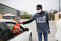 """Volunteer Tobi Babalola gives out a """"Hope Tote"""", Saturday, April 3, 2021 at Sam's Furniture in Springdale. Samaritan's Feet distributed approximately 720 pairs of shoes to pre-registered students from 18 elementary schools across Springdale in a """"drive-thru"""" event. Each recipient received a """"Hope Tote"""" drawstring book bag that contains a new pair of athletic shoes, socks, hygiene kit and a """"hope note"""" with an encouraging message submitted online from Samaritan's Feet supporters. Check out nwaonline.com/210404Daily/ for today's photo gallery. <br /> (NWA Democrat-Gazette/Charlie Kaijo)"""