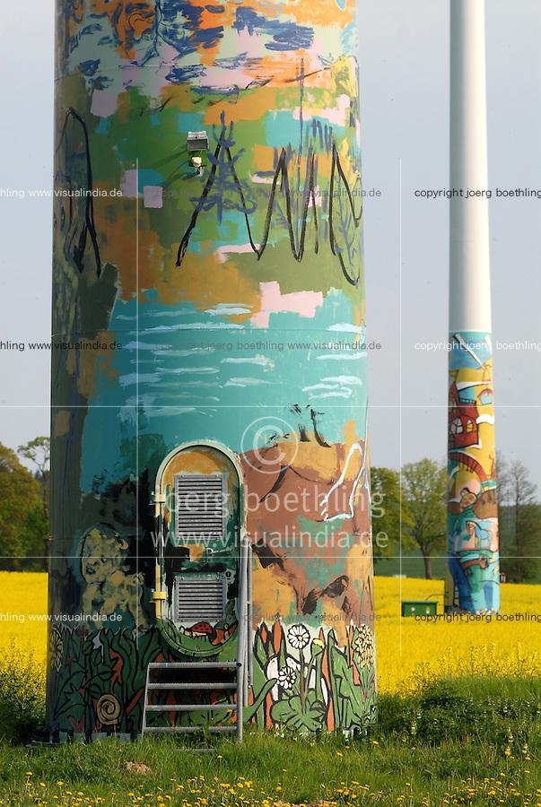 GERMANY, Wismar, village Luebow, yellow rape seed plant and Enercon windturbine with art painting / DEUTSCHLAND, Wismar, Rapsbluete und Windpark mit von Kuenstlern bemalten Enercon E-66 Windraedern in Lübow