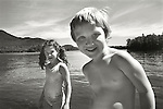Young boy and girl on shore smiling at camera. Blue Mountain Lake. 1976