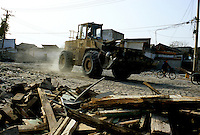 CHINA. Beijing. A digger clears the remnants of an old hutong (traditional homes) in the Qianmen district, destroyed to make way for new developments aimed at modernising the city for the 2008 Summer Olympics. 2005