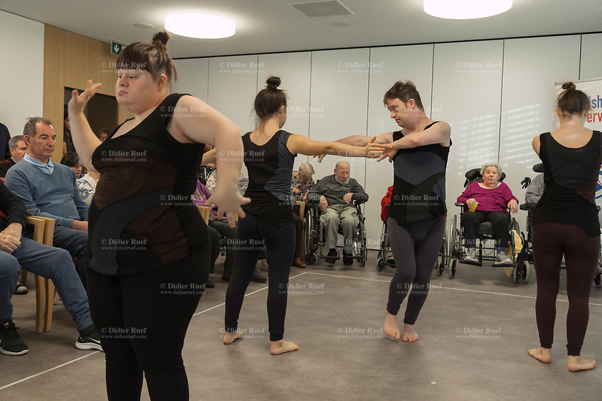 """Switzerland. Canton Ticino. Gordola. Casa Riposo (Retirement Home) Solarium. MOPS_DanceSyndrome is an independent Swiss artistic, cultural and social organisation operating in the field of contemporary dance and disability. It is composed only of Down dancers. Amedea Aloisi (L), Elisabetta Montobbio (LC), Simone Lunardi (RC) and Gaia Mereu (R) on stage during """"Choreus Numinis"""" show. Down syndrome (DS or DNS), also known as trisomy 21, is a genetic disorder caused by the presence of all or part of a third copy of chromosome 21 It is usually associated with physical growth delays, mild to moderate intellectual disability, and characteristic facial features. A group of elderly people, all seated in wheelchairs, look at the woman dancing. A retirement home – sometimes called an old people's home or old age home - is a multi-residence housing facility intended for the elderly. Gordola is a municipality in the district of Locarno. 29.11.2019 © 2019 Didier Ruef"""