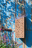 Wildbienen-Nisthilfe aus Hartholz, Massivholz, Holz. Als Regenschutz wird auf die angeschrägte Seite des Klotzes eine Plexiglasscheibe aufgeschraubt. Der Holzklotz wurde mit unterschiedlich dicken Bohrungen versehen, Wildbienen-Nisthilfen, Wildbienen-Nisthilfe selbermachen, selber machen, Wildbienenhotel, Insektenhotel, Wildbienen-Hotel, Insekten-Hotel
