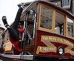 A man hangs off a San Francisco Cable Car.