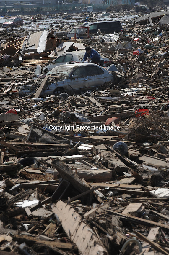 A man looks through the remains of his car that lies amongst the splintered remains of houses in the  town of Natori, after the Tsunami devastated the entire pacifc coastline of Japan after the earthquake and tsunami devastated the area Sendai, Japan.<br /><br />photo by Richard Jones/ sinopix