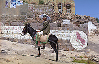 Boy riding a donkey in the town of Al-Hajjarah in the Heraz mountains. The rearing horse is the emblem used by the ruling General People's Congress party.