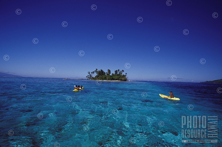 Chidren paddling a kayak in clear lagoon waters near a 'motu' islet off Moorea, Society Islands, French Polynesia