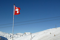 """Switzerland. Valais. Crans Montana. Winter ski resort. Ski lifts are carrying people to the top of the mountain, while other are skiing down the """"Bella Lui"""" slopes on a sunny day with blue sky. A swiss flag floats in the air. © 2005 Didier Ruef"""