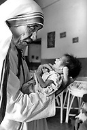 """Calcuta, India. April 04, 1975. Mother Teresa in her orphanage spending time with each of them. She takes long hours in the morning to talk and confront them. Mother Teresa (Agnes Gonxha Boyaxihu) the Roman Catholic, Albanian nun revered as India's """"Saint of the Slums,"""" was awarded the 1979 Nobel Peace Prize."""