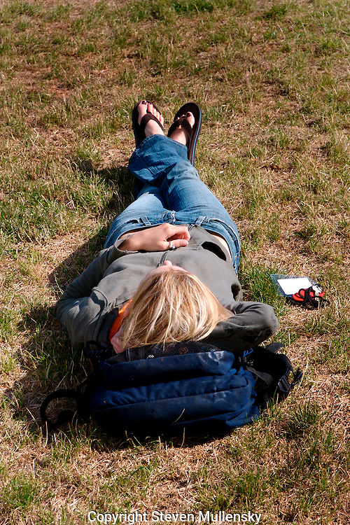 Snoozing in the summer sun is what is important for this young woman while taking a break from classes in writing at Fort Worden State Park.