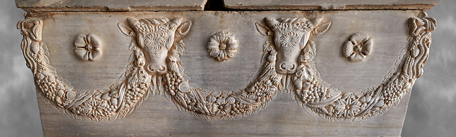 Roman relief sculpted garland sarcophagus with reliefs of bulls heads and garlands, 2nd century AD. Adana Archaeology Museum, Turkey. Against a grey background