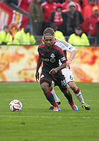 Toronto, Ontario - May 3, 2014: Toronto FC forward Jermain Defoe #18 and New England Revolution midfielder Scott Caldwell #6 in action during a game between the New England Revolution and Toronto FC at BMO Field.<br /> The New England Revolution won 2-1.
