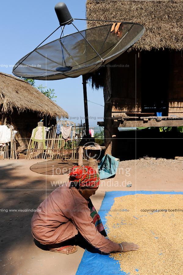 LAOS, province Oudomxay , village Houyta, Khmu woman dries rice in sun, the rice is used to prepare sticky rice as their staple food / LAOS Provinz Oudomxay Dorf Houyta , Ethnie Khmu , Frau trocknet Reis in der Sonne, die lokale Reissorte wird als Klebereis zubereitet und ist Grundnahrungsmittel