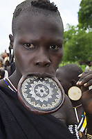 """Ethiopia. Southern Nations, Nationalities, and Peoples' Region. Omo Valley. Mursi tribe. Agro-pastoralist group. Nomadic. Mursi women are known as """"disk-lip"""" women. The bottom lip is slit along its full length and the front bottom row of teeth are pulled out to accomodate the ceramic disk which is handmade with a rim around which the stretched lip is pulled. The women are famed for wearing large plates in their lips (round clay plates placed into a cut in the lower lip) and ears. The disk is seen as a symbol of beauty and wealth, and often the younger girls will pierce and strech their ear-lobes, inserting a matching disk in the extended lobe. The Omo Valley, situated in Africa's Great Rift Valley, is home to an estimated 200,000 indigenous peoples who have lived there for millennia. Amongst them are 8'000 Mursi who dwell between the Omo and Mago rivers. Southern Nations, Nationalities, and Peoples' Region (often abbreviated as SNNPR) is one of the nine ethnic divisions of Ethiopia. 11.11.15 © 2015 Didier Ruef"""