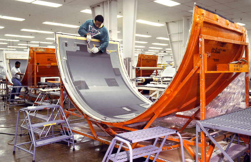 Workers prep aircraft components for final assembly and painting