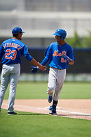 GCL Mets center fielder Stanley Consuegra (59) is congratulated by hitting coach Rafael Fernandez (23) as he rounds third base after hitting a home run in the top of the seventh inning during a game against the GCL Nationals on August 4, 2018 at FITTEAM Ballpark of the Palm Beaches in West Palm Beach, Florida.  GCL Nationals defeated GCL Mets 7-4.  (Mike Janes/Four Seam Images)