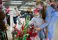 Andrea Nichols of Joplin, Mo. holds Magnolia Nichols, 3, as they look at decorations, shown with Alexander Nichols, 4,Thursday, October 15, 2020 at the Benton County Fairgrounds in Bentonville. The 4th annual Fall Y'all Craft Fair featured 40 vendors, half capacity to previous years, as well as local food trucks, photo opportunities and a pumpkin patch. The fair ends on Sunday. Check out nwaonline.com/2010013Daily/ for today's photo gallery. <br /> (NWA Democrat-Gazette/Charlie Kaijo)