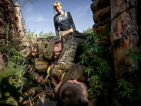 Natalia Voronkova, a volunteer who offers support and basic first aid training for Ukrainian government forces fighting Russian-backed separatists in the east of the country, looks on as a group of soldiers role-play real life medical situations that they may encounter on the frontlines.