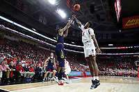 RALEIGH, NC - JANUARY 9: Juwan Durham #11 of the University of Notre Dame shoots over Manny Bates #15 of North Carolina State University during a game between Notre Dame and NC State at PNC Arena on January 9, 2020 in Raleigh, North Carolina.