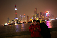CHINA. Shanghai. Two tourists on the Bund with the famous PuDong skyline behind them. Shanghai is a sprawling metropolis or 15 million people situated in south-east China. It is regarded as the country's showcase in development and modernity in modern China. This rapid development and modernization, never seen before on such a scale has however spawned countless environmental and social problems. 2008