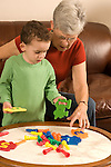 Grandmother in late 70s playing with 3 year old grandson and counting peg puzzle toy vertical Caucasian