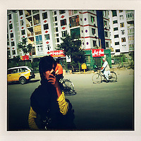 A woman, standing on a street in front of a housing complex, holds her veil to her mouth to avoid fumes.