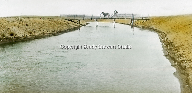 Jerome ID:  Horse-drawn carriage traveling over the irrigation canal.  Brady Stewart and three friends went to Idaho on a lark from 1909 thru early 1912.  As part of the Mondell Homestead Act, they received a grant of 160 acres north of the Snake River.  Brady Stewart photographed the adventures of farming along with the spectacular landscapes. To give family and friends a better feel for the adventure, he hand-color black and white negatives into full-color 3x4 lantern slides.  The Process:  He contacted a negative with another negative to create a positive slide.  He then selected a fine brush and colors and meticulously created full-color slides.