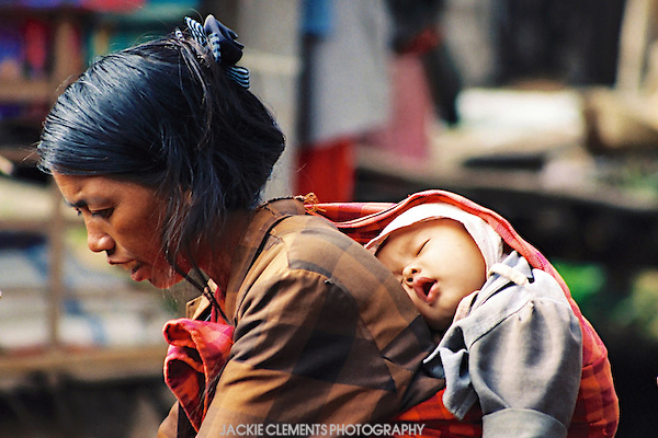 A woman carries her baby on her back as she shops in the market.