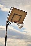 Broken basketball backboard against sky.