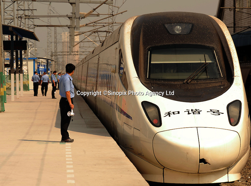 A conductor stands on platform next to high-speed rail in Changchun, China. China is the first and only country to have commercial high-speed train service on conventional rail lines that can reach a top operational speed of 350km/h (217mph)..31 Aug 2010.