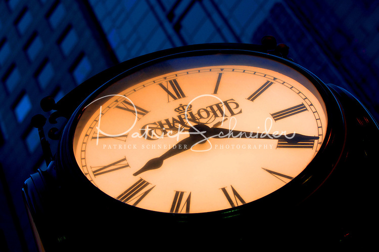 A clock glows at twilight in uptown Charlotte, NC.