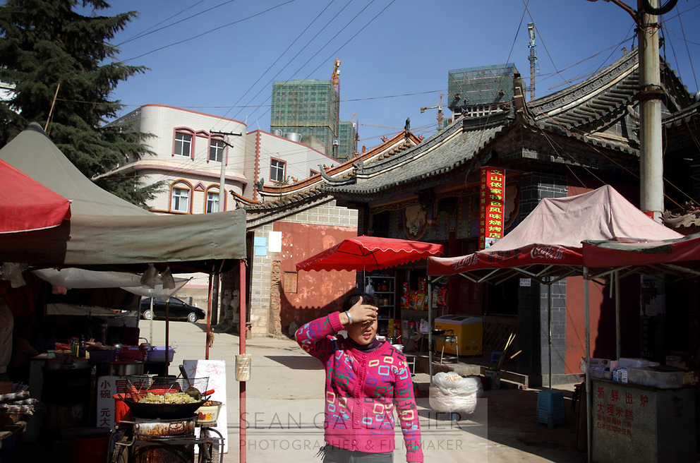 New developments loom over the remaining traditional buildings in Zijun village, home of the Samatao minority.