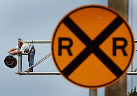 Florida East Coast Railroad employee Paul Crosby, of Daytona Beach, uses a wrench as he tightens a new light assembly he installs on the railroad crossing 18 feet above  east Granada Boulevard in Ormond Beach Wednesday may 28, 2003. The replacement of the warning signals is routine maintenance in place to keep the signal light technology updated. Crosby and his co-worker complete the replacement of the signals on the west side of the tracks during the 2 1/2 hour project, they will return for the east crossing gate at another date.(Kelly Jordan)..**FOR STAND ALONE FEECH**
