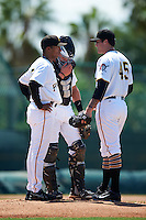 GCL Pirates pitching coach Elvin Nina (35) talks with relief pitcher Jacob Taylor (45) and catcher Paul Brands (25) during a game against the GCL Yankees East on August 15, 2016 at the Pirate City in Bradenton, Florida.  GCL Pirates defeated GCL Yankees East 5-2.  (Mike Janes/Four Seam Images)