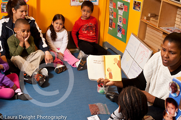 Education Preschool 3 year olds with two teachers at circle time teacher reading book