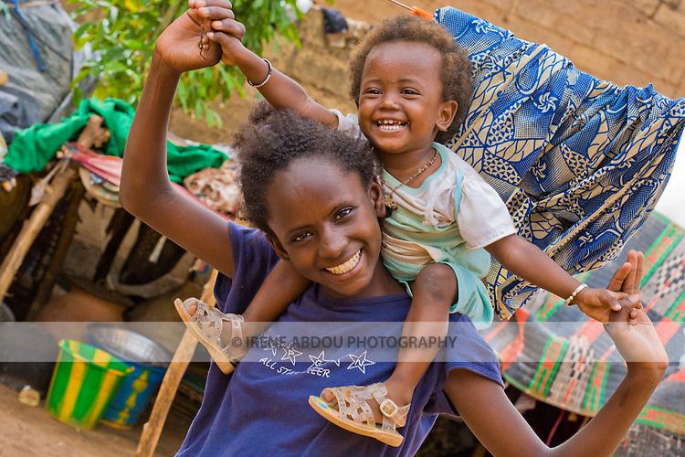 A young Fulani girl twirls her younger sister on her shoulders in Ouagadougou, Burkina Faso.