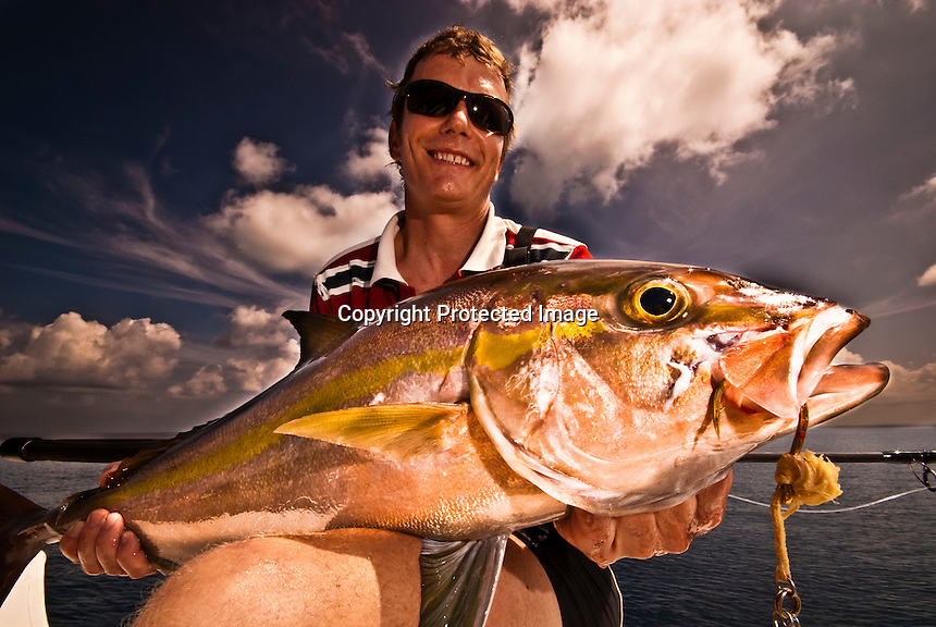 Maldives, Indian Ocean November 2008. Fisherman in his 40s holding an Amberjack (Seriola rivoliana), a member of the carangide family found in all temperate waters.