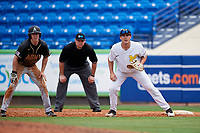 Michigan Wolverines first baseman Matthew Schmidt (9) holds Jacob Hurtubise (39) as umpire Bob Lothian looks on during a game against Army West Point on February 18, 2018 at Tradition Field in St. Lucie, Florida.  Michigan defeated Army 7-3.  (Mike Janes/Four Seam Images)