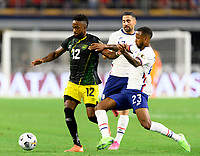 DALLAS, TX - JULY 25: Kellyn Acosta #23 of the United States attempts to strip the ball from Junior Flemmings #12 of Jamaica during a game between Jamaica and USMNT at AT&T Stadium on July 25, 2021 in Dallas, Texas.