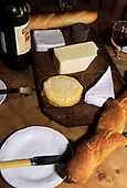 Brusvily, Britanny, France. Cheeses on a cheese board, bread, knife, bottle and glass of wine.