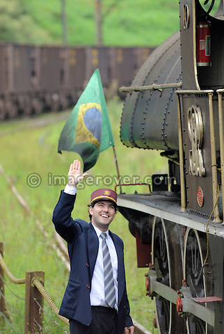 Train attendent accompanying the historic steam train at Paranapiacaba station; near Sao Paulo, Brazil. In 1856 the British-owned Sao Paulo Railway Company was awarded the concession to operate a rail line between the port of Santos and Jundai, 70km north of Sao Paulo city, in what was then a developing coffee-growing region. The 139km line was completed in 1867, remaining under British control until 1947. Overcoming the near-vertical incline of the Serra do Mar that separates the interior of the state from the coast, the line was using the largest funicular system in the world and was regarded as an engineering miracle. --- No releases available.