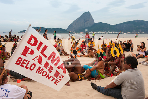 """Indigenous people and others are beginning to assemble the human banner on Flamengo beach with the Sugarloaf in the background to protest about the construction of hydroelectric dams on Brazil's rivers. One participant carries a flag, """"Dilma Pare Belo Monte"""" - """"Dilma [Brazil's president] Stop Belo Monte"""". The People's Summit at the United Nations Conference on Sustainable Development (Rio+20), Rio de Janeiro, Brazil, 19th June 2012. Photo © Sue Cunningham."""