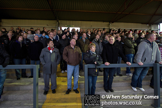 Hyde 1 Stalybridge Celtic 1, 26/12/2011. Ewen Fields, Conference North. Spectators in the enclosure watching the action at Ewen Fields, Hyde, as Hyde (in red) take on Stalybridge Celtic in a Conference North fixture. The match, between the teams occupying the top two places in the division, ended one-all in front of 1868 spectators, Hyde's largest home attendance in 15 years. Ewen Fields is used by Manchester City reserves for matches and has been rebranded in city's colours and with their sponsors advertising around the ground, with the club changing its name from Hyde United to the present one. Photo by Colin McPherson.