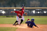 Second baseman Javier Nazario (11) fields a throw down from the catcher as Yahir Acevedo (1) safely steals the base during the Perfect Game National Underclass East Showcase on January 23, 2021 at Baseball City in St. Petersburg, Florida.  Shortstop Adriel Vega Santiago (15) backs up the play.  (Mike Janes/Four Seam Images)