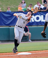 Third baseman Rob Lyerly (16) of the Charleston RiverDogs twists and turns to catch a pop fly in a game against the Greenville Drive on May 27, 2010, at Fluor Field at the West End in Greenville, S.C. Photo by: Tom Priddy/Four Seam Images