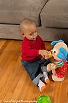 18 month old toddler boy pretend play feeding stuffed toy, giving it drink from cup