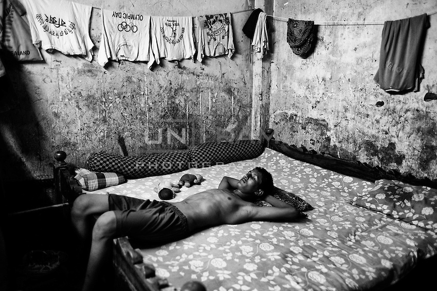 Zakir rests in  his house. One year back, Zakir got a chance to study at BKSP with full scholarship but his father denied him to continue to study because doing so he wouldn't have been able to support his family. Dhaka, Bangladesh.