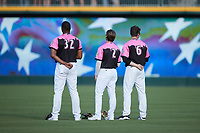 (L-R) Charlotte Knights outfielders Eloy Jimenez (32), Luis Gonzalez (2), and Blake Rutherford (6) stand for the National Anthem prior to the game against the Gwinnett Stripers at Truist Field on July 17, 2021 in Charlotte, North Carolina. (Brian Westerholt/Four Seam Images)